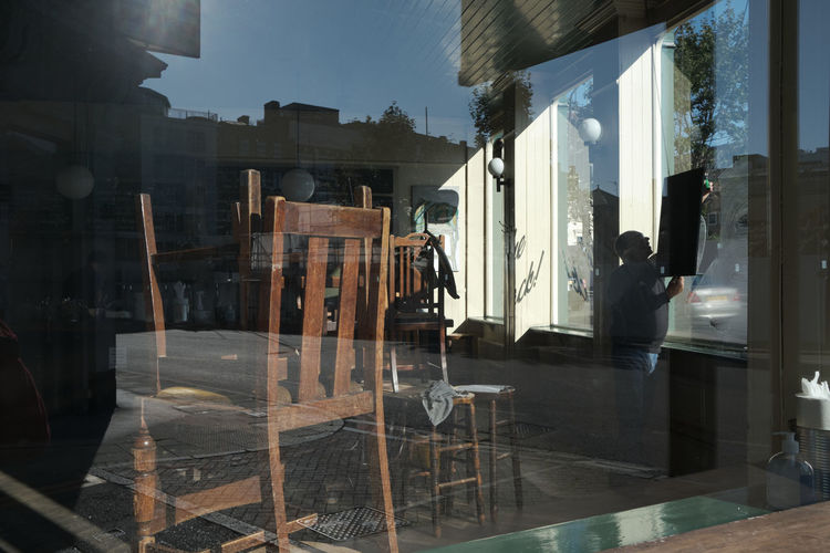 Reflection of man standing on glass window