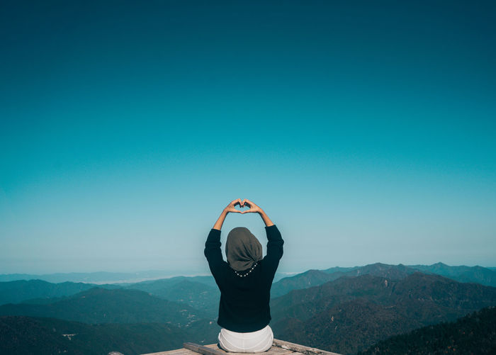 Rear view of woman making heart shape with hands while sitting on mountain