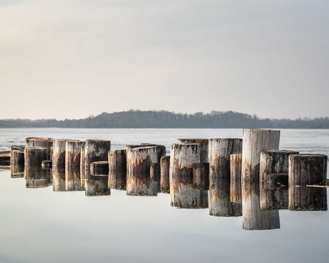 Panoramic view of wooden posts in lake against clear sky