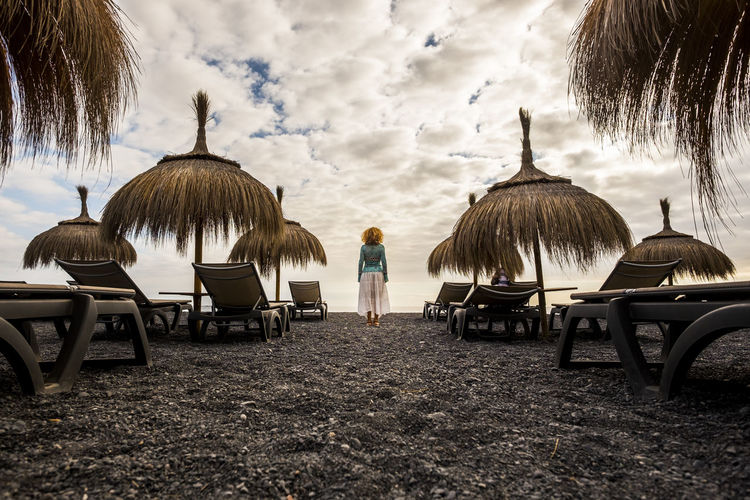 Woman standing amidst thatched roof at beach