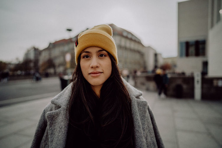 Portrait of woman wearing hat standing in city