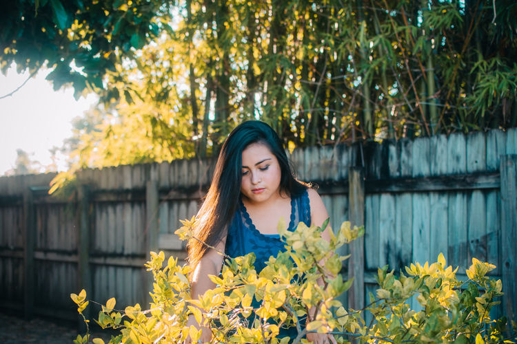 Young woman standing by plants against wooden fence