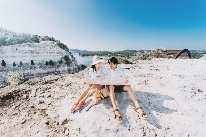 People sitting on land against sky