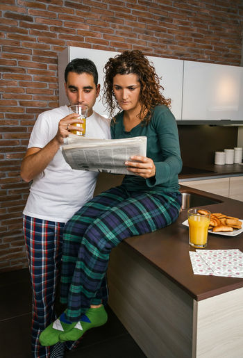 Couple having breakfast in the kitchen and reading the newspaper Vertical Drinking Socks Modern Brick Wall Croissant Surprised Serious Portrait Biscuits Sharing  Morning Together Orange Juice  Indoor Real Two Young Woman Curly Hair Wife Standing People Married Man Male Lifestyle Husband Talking Caucasian Home Girl Female Entertainment Watching Concerned Kitchen Worried Looking Newspaper News Reading Breakfast Pajama Couple Interested