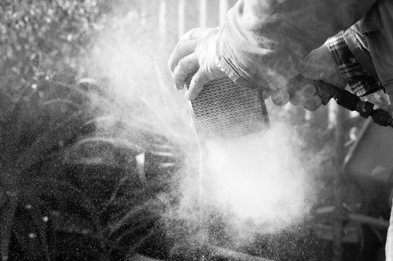 Cropped Image Of Worker Removing Dust