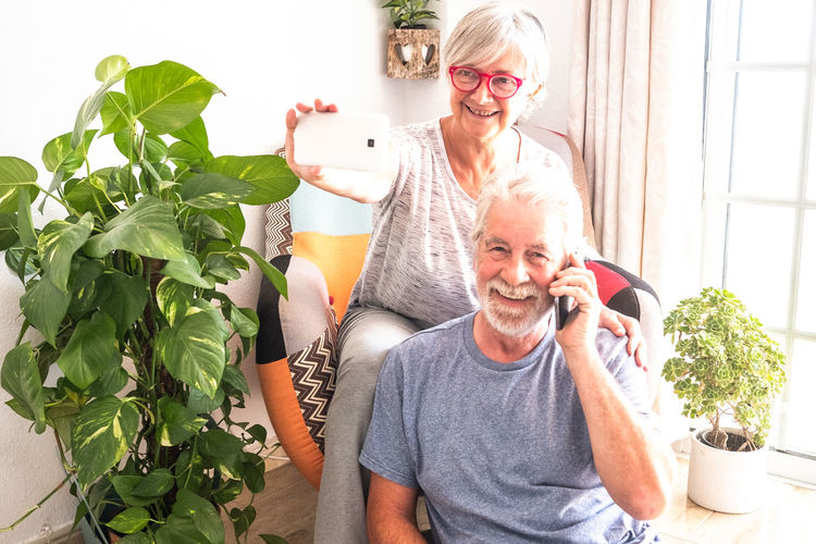 Senior couple talking at the phone and taking a selfie. Two adult people with gray and white hair sitting in armchair. Natural plants in background. Bright window 70 Years Activity Adult Aged Armchair Background Beard Bright Casual Caucasian Connection Couple Decoration Domestic Elderly Emotion Enjoying Eyeglasses  Grandparents Gray Hair Hands Home Hug Inside Light Love Man Mobile Phone Natural News Old Pensioner Photo Plant Positivity Retired Retirement Senior Serene Sitting Smiling Sun Sunlight Tablet Technology Tenderness White Window Woman Two People