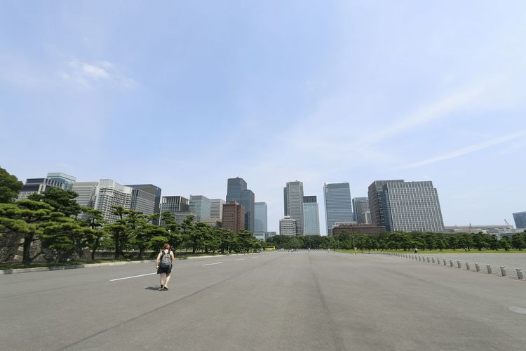 Rear view of man walking on road in city