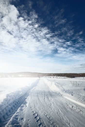 Tire tracks on snow covered land against sky
