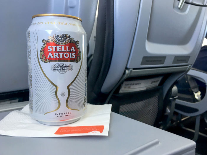 Brussels, Belgium - 15 August 2017: Aluminum can of Stella Artois on a white napkin sitting on folding seat tray in economy class during a Brussels Airlines flight. Can of beer on a airplane flight. AirPlane ✈ Flights Stella Artois Stella ❤ Airplane Airplanes Brussels Airlines Brussels Belgium Flight Flight ✈ Stella Stellaartois