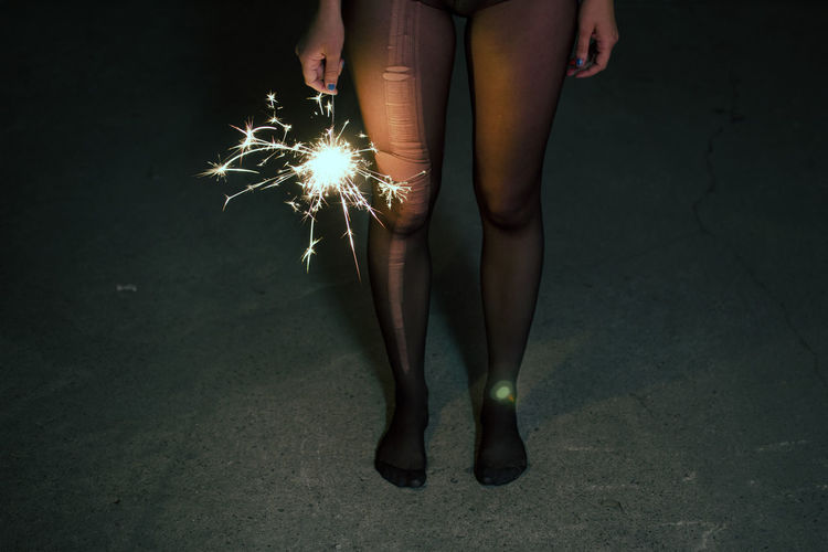 Low Section Of Woman With Sparkler Standing On Walkway At Night