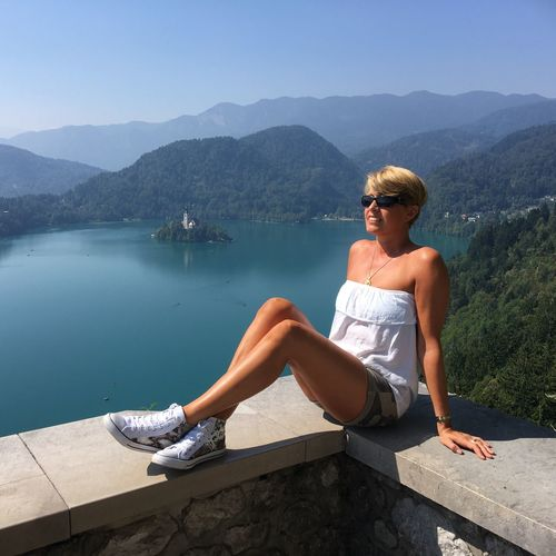 Full Length Of Woman Sitting On Retaining Wall Against Lake And Mountains