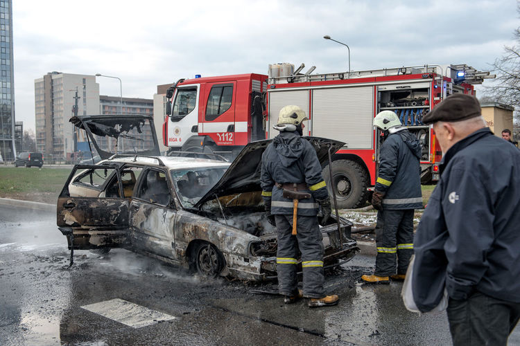 Firefighters standing by burnt car on road in city