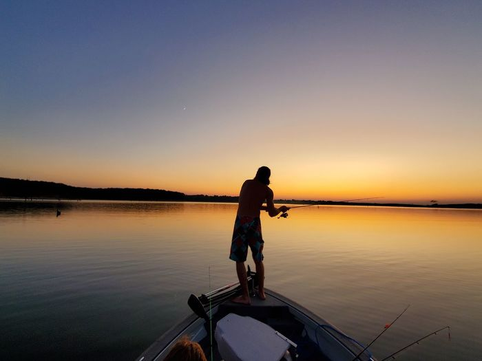 Silhouette fisherman fishing while standing on boat in lake against clear sky
