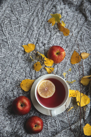 Cozy and soft autumn background. cup of tea and warm knitted sweater.