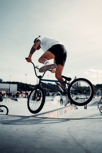 Man riding bicycle on street against sky
