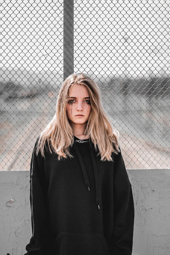 Portrait of beautiful young woman standing against fence