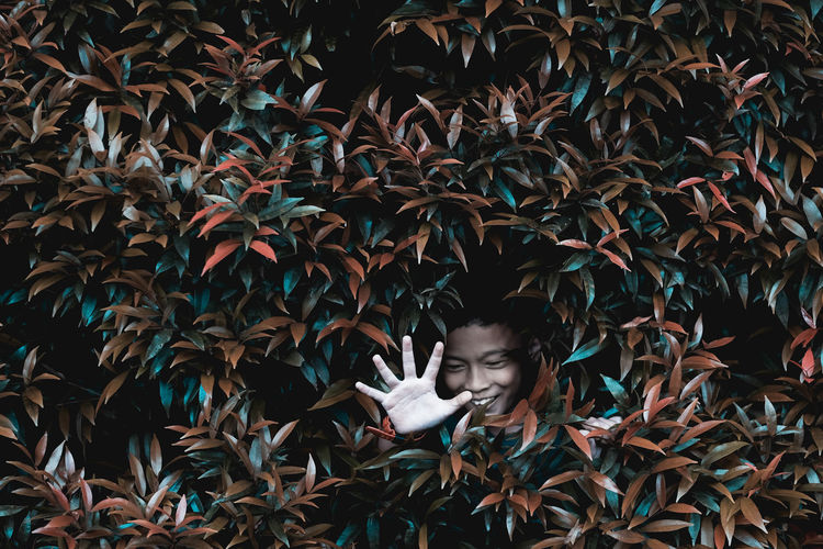 Happy boy showing stop gesture amidst plants leaves