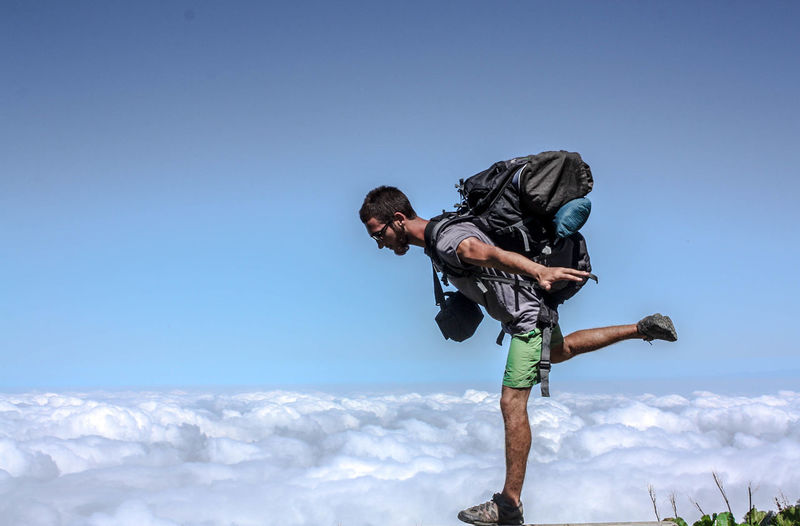 Hiker standing on cliff against cloudy sky
