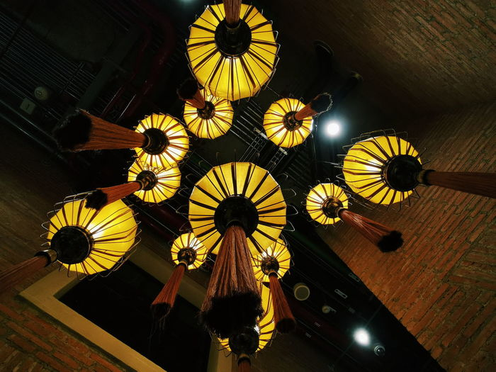 Low angle view of illuminated chandelier hanging on ceiling in building