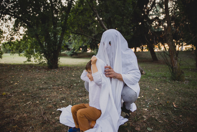 Cute boy with person wearing ghost costume in park at sunset during halloween
