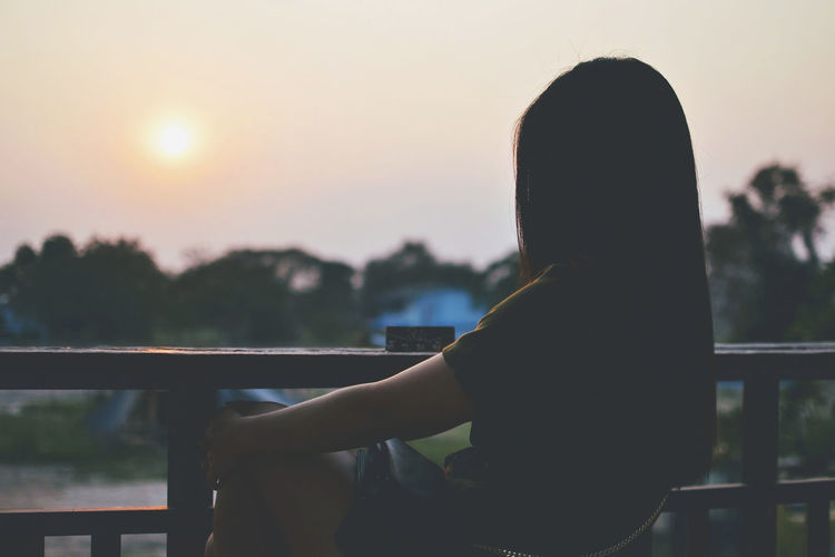Side view of silhouette woman sitting by railing in balcony at sunset