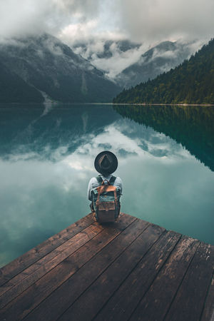 Traveler with denim jacket, black hat and a brown backpack sitting over wooden bridge on the lake at moody sunrise. Travel and active life concept at Lake Plansee, Tirol, Austria Hat Plansee Backpack Beauty In Nature Boathouse Cloud - Sky Day Denim Jacket Idyllic Lake Mountain Nature Non-urban Scene One Person Outdoors Pier Reflection Remote Scenics - Nature Sky Tranquil Scene Tranquility Traveler Water Wood - Material