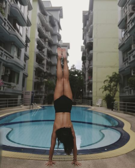 Upside Down. Swimming Pool Water One Person Exercising Adults Only Healthy Lifestyle Only Women One Woman Only People Lifestyles Sport Portrait Outdoors Architecture Vacations Women Full Length Day Girls Beautiful Woman Flexibility Exercising Yoga Handstand  Yoga Pose