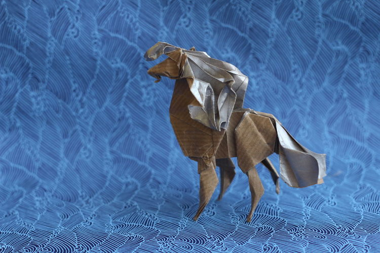 Close-up of paper horse on blue backdrop