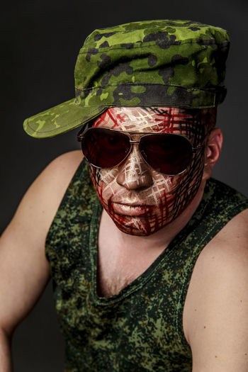 Portrait of man with face paint wearing sunglasses and cap