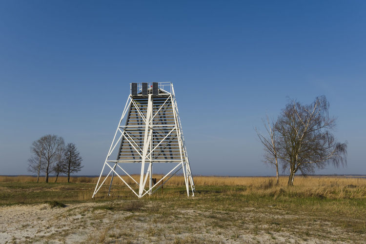 Low angle view of tower on field against clear blue sky