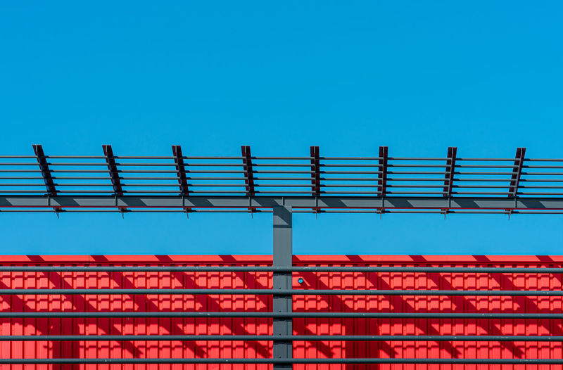 Low angle view of railings against building against clear blue sky