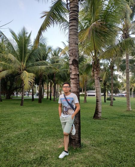 Full length portrait of young man standing on palm trees