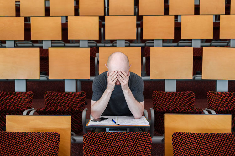 Frustrated man sitting in examination hall