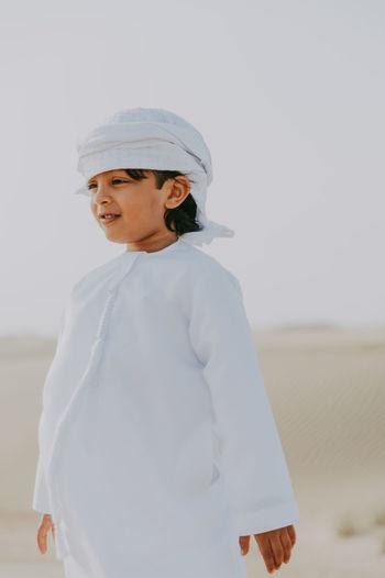 Cute smiling boy standing at desert