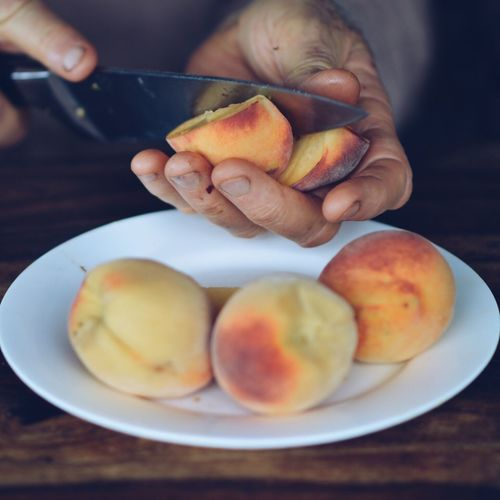 Cropped image of hand cutting peach on table