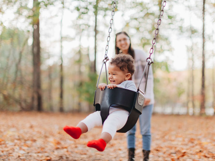 Mother and daughter playing on swing at playground