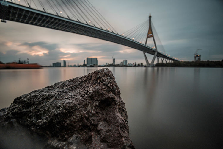 Low angle view of bridge over river in city against cloudy sky