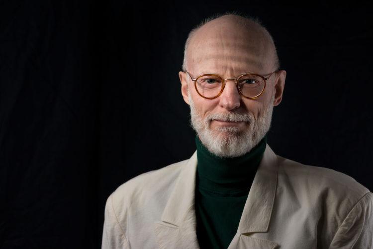 Portrait Of Smiling Senior Man Wearing Suit Against Black Background