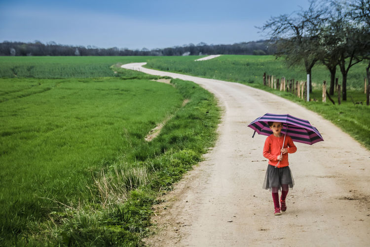 Footpath Childhood Day Direction Field Full Length Girl Land Landscape Nature One Person Outdoors Plant Protection Rain Real People Road The Way Forward Transportation Tree Umbrella Walking Walking Alone...