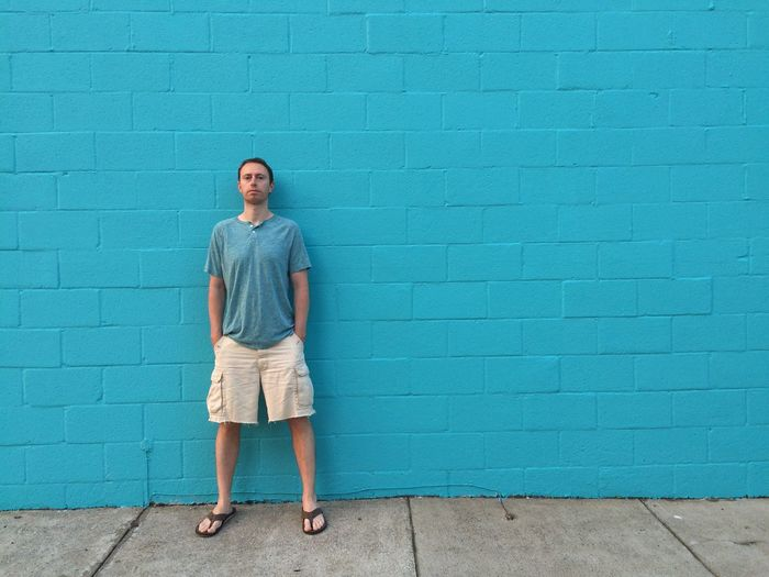 Portrait of man standing on blue wall