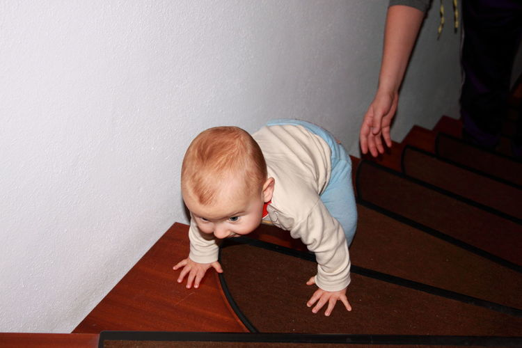 High angle view of baby boy climbing on steps at home