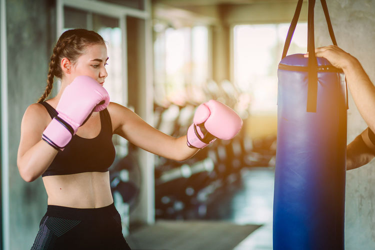 Young woman boxing in gym