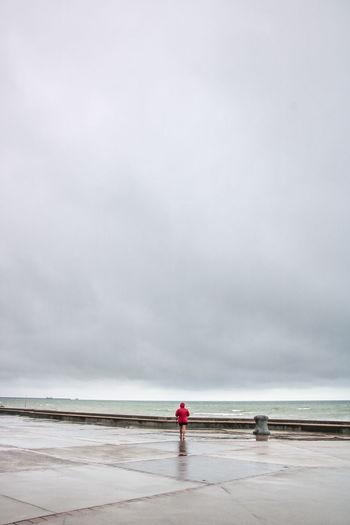 Rear view of woman walking on promenade against cloudy sky