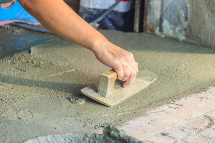 Midsection of man working on concrete wall