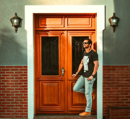 Full length of young man standing by closed door