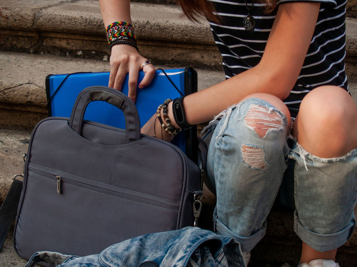 Midsection of woman putting file in bag while sitting outdoors