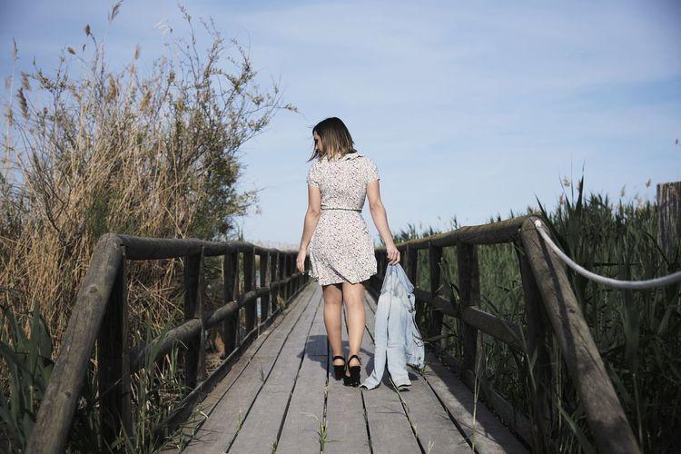 Rear view of woman standing on footbridge against sky