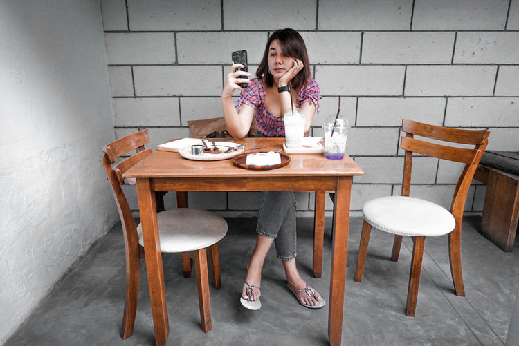 Full length of woman sitting on table at cafe