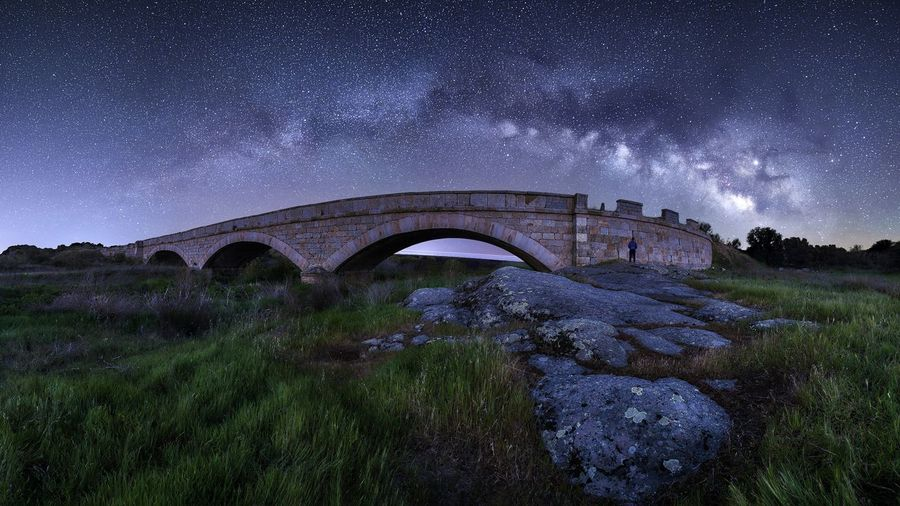 Arch bridge against sky at night