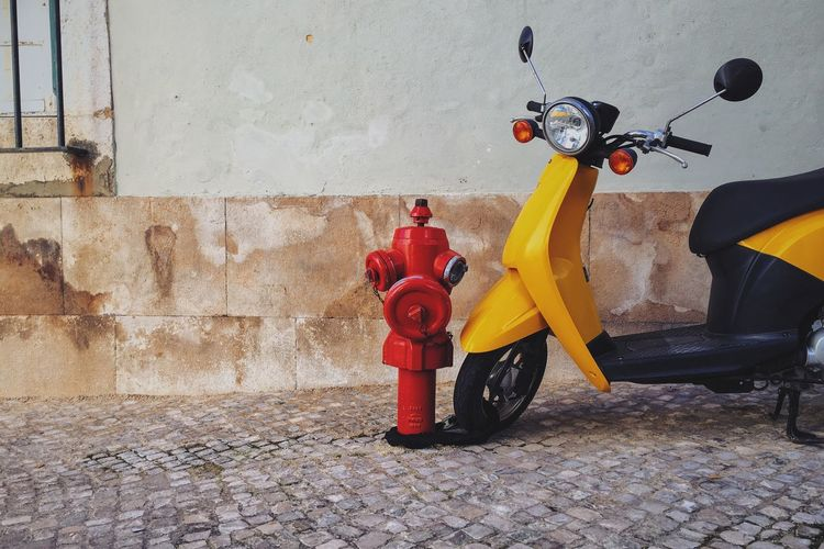 Motor Scooter By Fire Hydrant On Footpath By Wall
